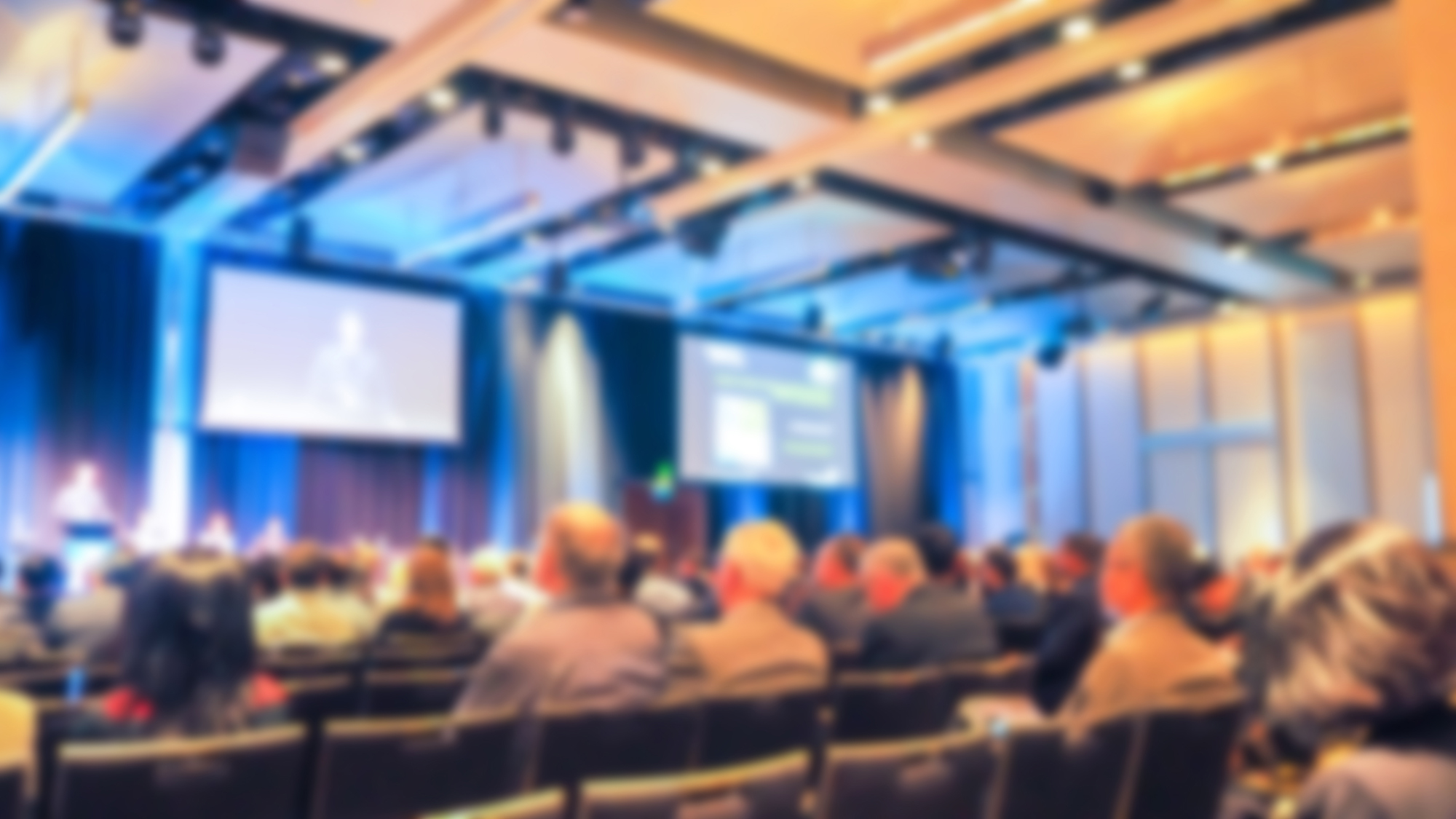 Fuzzy image of speaker presenting on stage under two projection screens