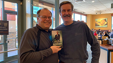 Small photo of Marty Dickinson and Jack Zoellner holding his new book, The Magical Manager