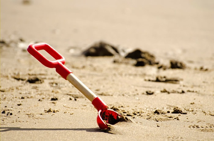 Shovel in sand on a beach to signify starting a business.